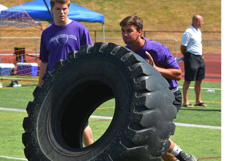 by: TIMES PHOTO: MATT SINGLEDECKER - Sunset senior offensive lineman Joe Peterson flips a 300-pound tire at the Metro Area Linemen Challenge at Tualatin High School. Peterson played mostly defense last year but could see time on both sides of the football.