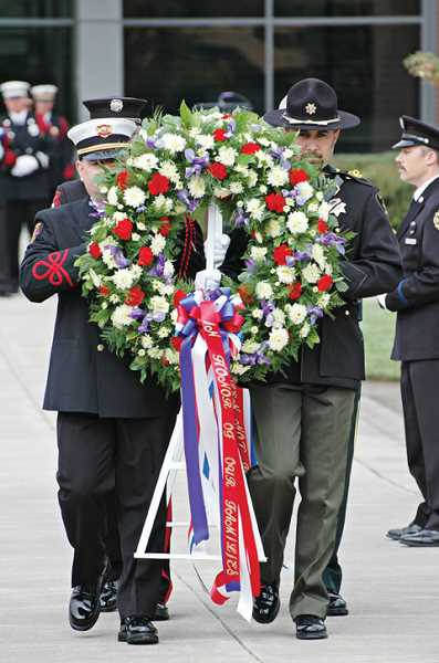 by: SUBMITTED PHOTO - Fire officials carry a wreath to remember fallen firefighters.