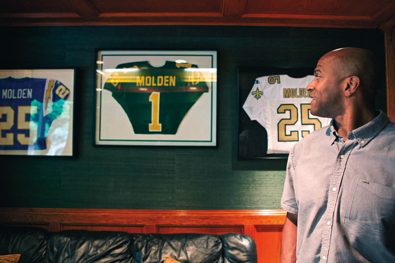 Photo Credit: TRIBUNE PHOTO: JAIME VALDEZ - Alex Molden looks at the framed jerseys of the teams he played for in the NFL, along with the jersey he wore as an Oregon Duck.
