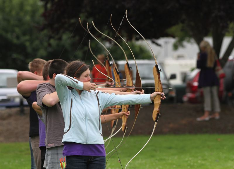 Photo Credit: HILLSBORO TRIBUNE PHOTO: AMANDA MILES - Anika Gering, 12, and several other students draw back their bows during a free lesson sponsored by the North Plains Public Library.