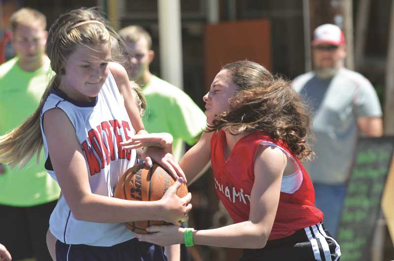 Photo Credit: COREY BUCHANAN - Two ballers in the 12-13 division fight for posession.