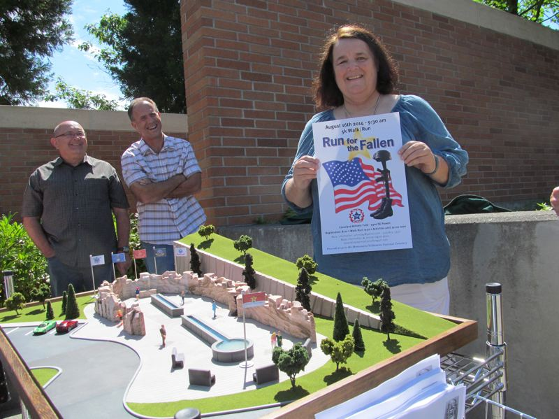 Photo Credit: PHOTO BY ELLEN SPITALERI - Terry Carroll holds a poster promoting the upcoming Run for the Fallen. She is standing in front of the proposed model for the Gold Star Memorial, constructed by Gary Pitman, owner of Proof of Concept in Vancouver, Wash., left, and his employee Todd Miller.