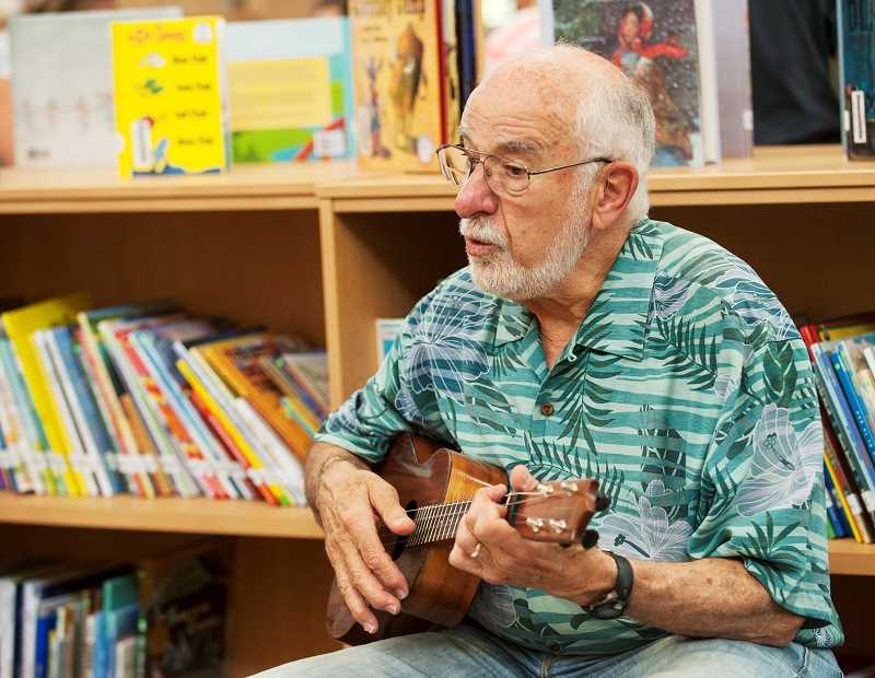 Photo Credit: SPOKEMAN PHOTO: JOSH KULLA - Gene Nudelman, a volunteer at Lowrie Primary School, spent time sharing his musical gifts with children during the schools open library hours in July.