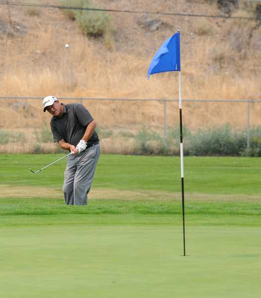 Photo Credit: LON AUSTIN/CENTRAL OREGONIAN - eff Storm chips onto the 15th green during the second day of the Meadow Lakes Men's Championship. Storm won the event with an even-par score of 144 for 36 holes.