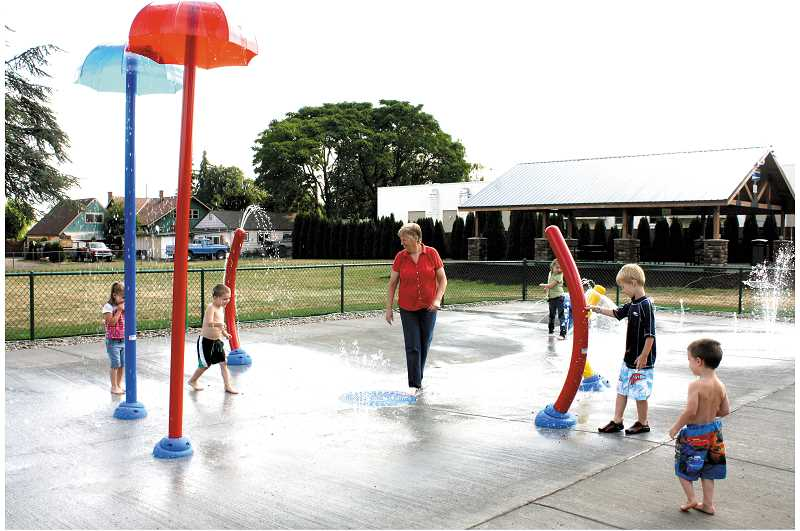 Photo Credit: PEGGY SAVAGE - Molalla Mayor Deborah Rogge joins the first kids to test out Molalla's renovated Fox Park Splash Pad Friday.