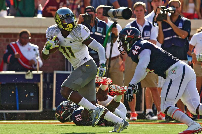 Photo Credit: TRIBUNE FILE PHOTO: JAIME VALDEZ - Oregon's Bralon Addison breaks away from Virginia defenders for a touchdown last season.