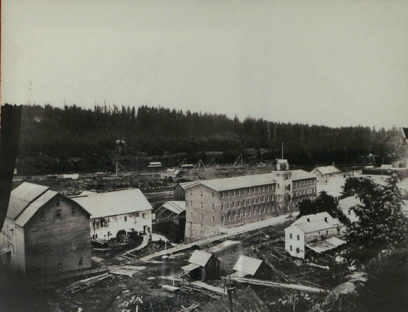Photo Credit: PHOTO COURTESY: CLACKAMAS COUNTY HISTORICAL SOCIETY - 1870s: The Holladay lot in front of the newly rebuilt Oregon City Woolen Mills had a wooden ramp leading off the Oregon & California Railroad track (foreground, out of picture), dropping to ground level to a path to the Imperial Mills.