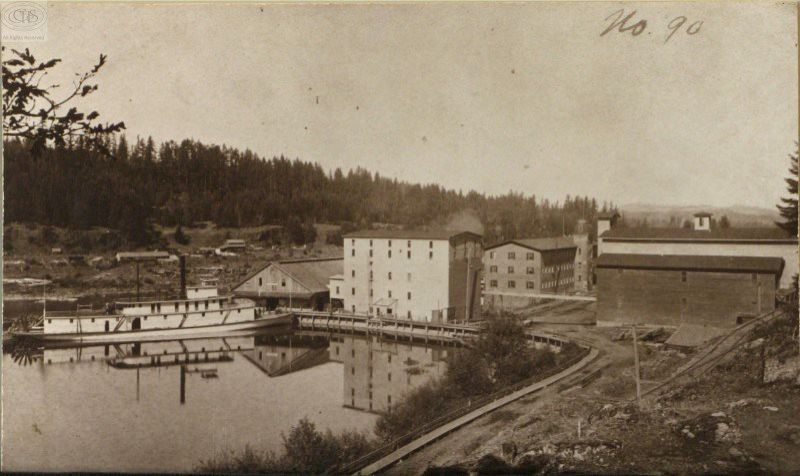 Photo Credit: PHOTO COURTESY: CLACKAMAS COUNTY HISTORICAL SOCIETY - 1880s: The newly constructed warehouse (1880 front) and grain elevator (1883 rear), railroad side track, and iron conveyor over and above Main Street.
