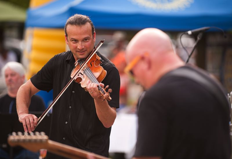 Photo Credit: SPOKESMAN PHOTO: JOSH KULLA - Violinist Aaron Meyer teams up for a back and forth solo with guitarist Tim Ellis July 31 at Town Center ePark in Wilsonville.