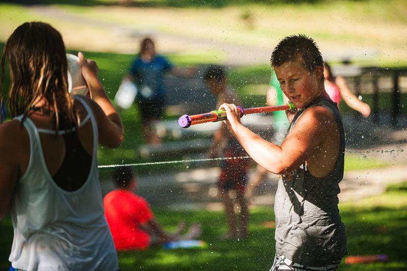Photo Credit: SPOKESMAN PHOTO: JOSH KULLA - A stream of water narrowly misses a water fight participant.
