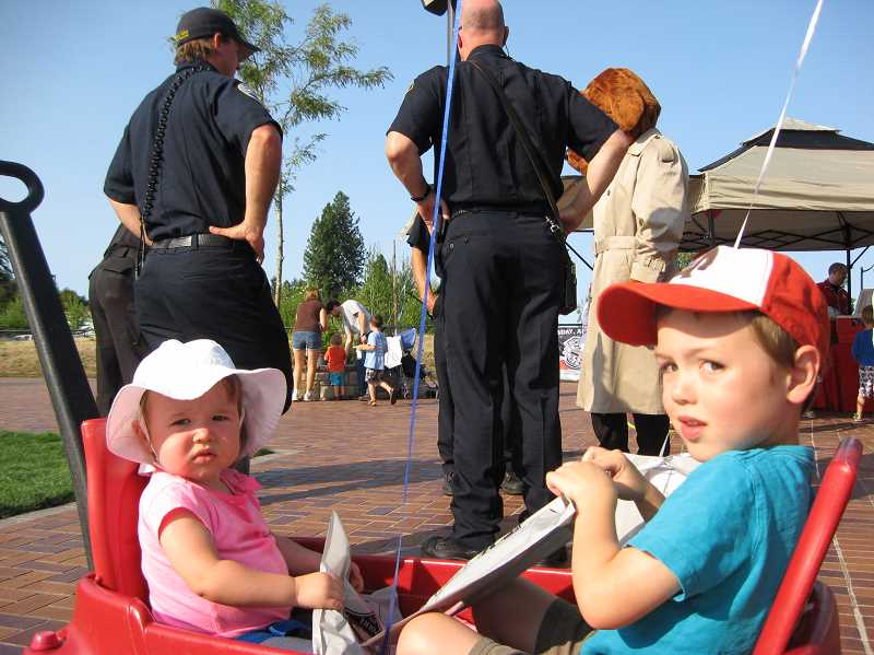 Photo Credit: GAZETTE PHOTO: RAY PITZ - Addison and Paxton Perkins of Sherwood hold onto goodie bags while McGruff the Crime Dog and firefighters from Tualatin Valley Fire & Rescue chat in the background during National Night Out held at Sherwood's Cannery Square Plaza Aug. 5.