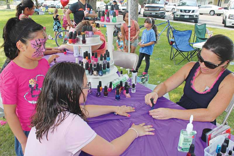 Photo Credit: HOLLY M. GILL - The Our Community in the Park event on Saturday was the first big event of a busy August. Above, volunteer Karen Affeldt polishes the nails of 11-year-old Victoria Hester, of Madras.