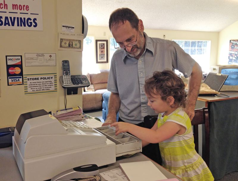 Photo Credit: SUBMITTED PHOTO - 2-year-old Miriam Gouz helps her grandfather, Larry Gouz, as he opens the till at Expressions Futons and Furniture. Larry Gouz opened the store 25 years ago after moving from New York to Oregon, and in that time has worked alonside his wife and two children.