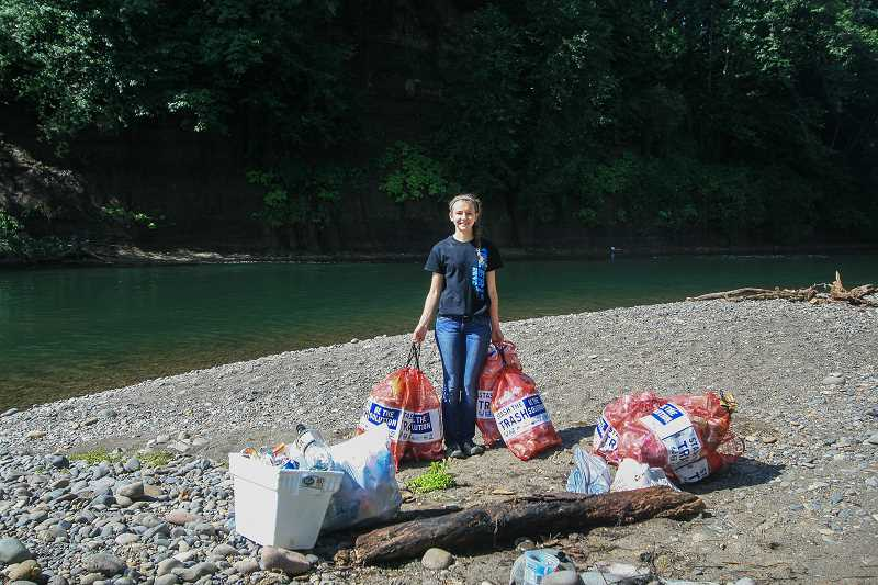 Photo Credit: CONTRIBUTED PHOTO - Clackamas High School student volunteer Amber Harvey stands with reusable litter bags from the Clackamas River Basin Council's Stash the Trash Program, which encourages river-goers to remove trash they bring in.