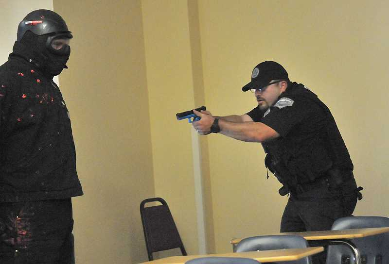 Photo Credit: REVIEW PHOTO: VERN UYETAKE - During a training exercise, Officer Ben Schneider faces off against a bad guy (Community Service Officer Brock Rosenthal).