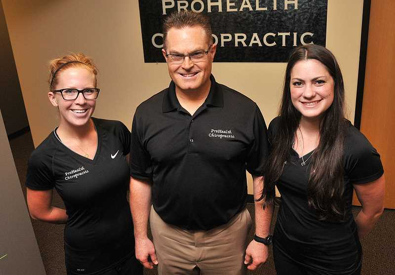 Photo Credit: STAFF PHOTOS: VERN UYETAKE - Jeff Robinson, center, with ProHealth Chiropractic staff members.