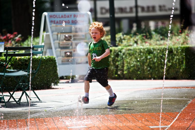 Photo Credit: TRIBUNE PHOTO: JAIME VALDEZ - Four-year-old Alex Figu runs through the fountain at  Holladay Park in Northeast Portland, where every day programming and events are expected to turn a little-used public space into a destination.