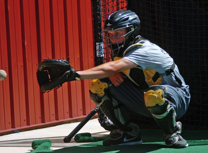 Photo Credit: DAN BROOD - CATCHING ON -- Zak Taylor, a Sherwood High School senior-to-be, grabs for the ball during a bullpen session last week. Taylor has given a verbal commitment to play college baseball at Oregon State University.