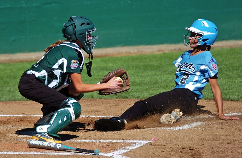 Photo Credit: DAN BROOD - PLAY AT THE PLATE -- Central catcher Jordyn Severns (left) forces out Tigard/Tualatin City's Kendra Zuckerman at home plate in the first inning of Thursday's Little League World Series softball game.