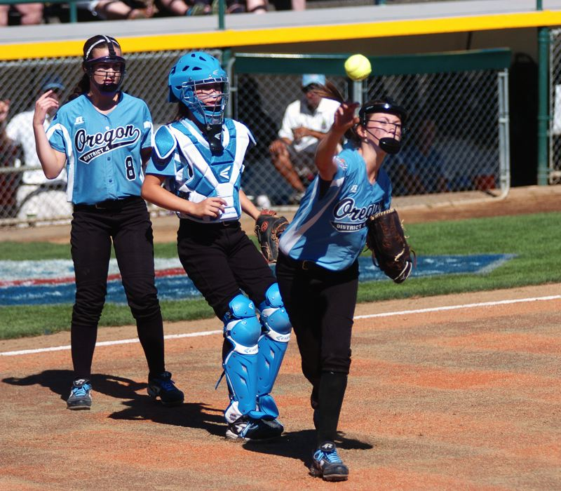Photo Credit: DAN BROOD - FOR THE DEFENSE -- Tigard/Tualatin City pitcher Elizabeth Hillier (right), with catcher Alexis Klum and third baseman Brooke Clinton behind her, makes a throw to first base after fielding a bunt.