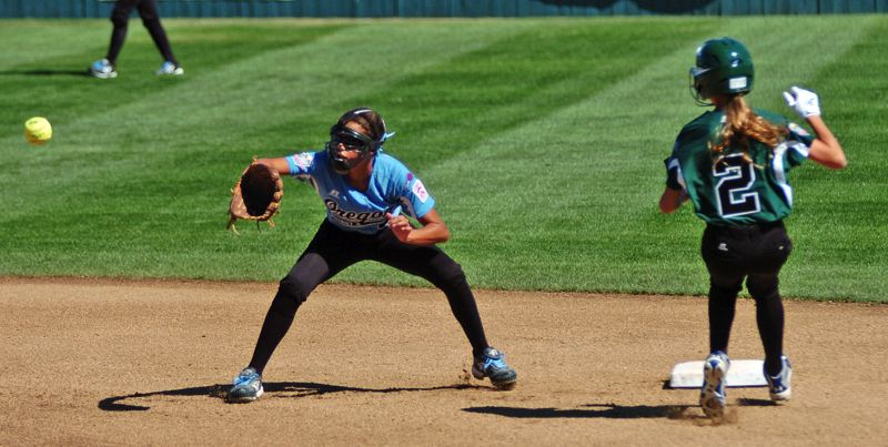 Photo Credit: DAN BROOD - WORLD SERIES ACTION -- Tia Cordts (left), playing at shortstop for Tigard/Tualatin City, looks to grab the ball as Central's Elizabeth Bickar heads to second base.