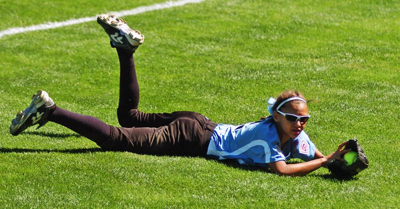 Photo Credit: DAN BROOD - WEB GEM -- Tigard/Tualatin City right fielder Kendra Zuckerman hits the ground after making a spectacular diving catch of a foul ball in Thursday's Little League Softball World Series game.