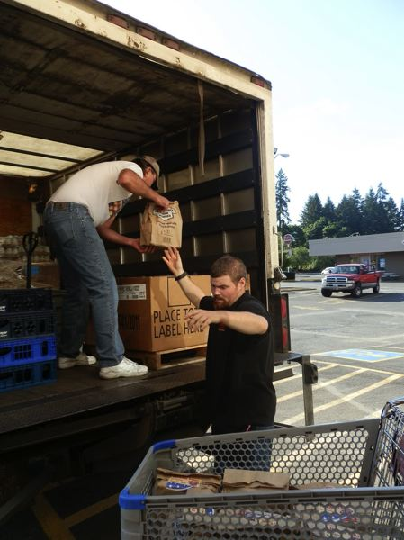 Photo Credit: COLUMBIA PACIFIC FOOD BANK PHOTO - Volunteers with Columbia Pacific Food Bank load a truck with food bags. The food bank distrubutes more than 700,000 pounds of food a year to the county's residents in need.