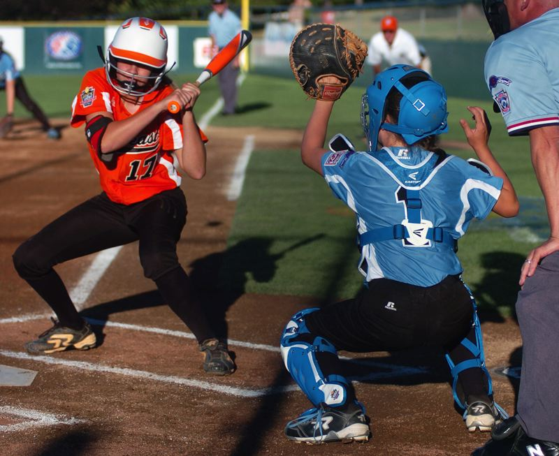 Photo Credit: DAN BROOD - BEHIND THE PLATE -- Tigard/TC catcher Alexis Klum grabs the pitch with Georgia's Ralee Weaver at the plate.