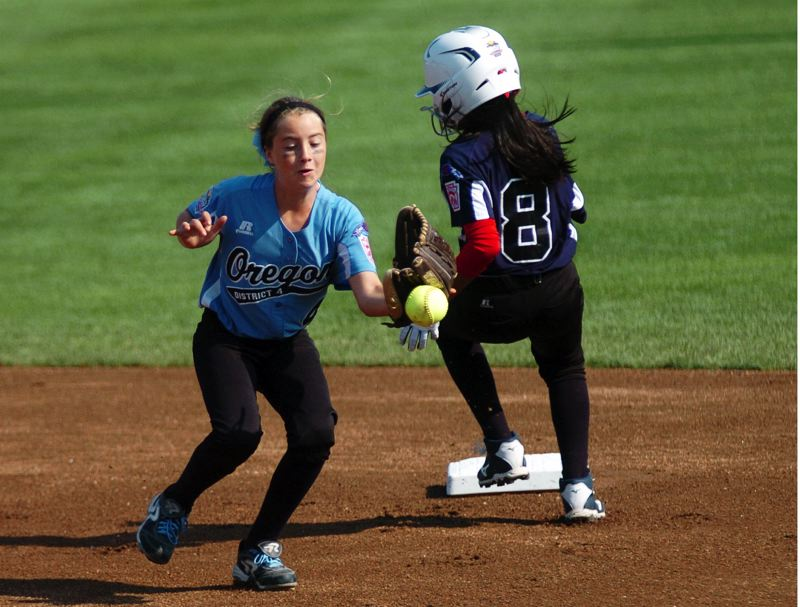 Photo Credit: DAN BROOD - THERE IT IT -- Tigard/TC shortstop Bella Valdes (left) goes for the ball while Puerto Rico's Omaris Torres heads to second base in Sunday's Little League Softball World Series game.