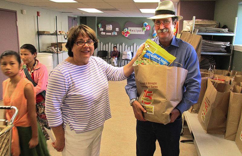 Photo Credit: OUTLOOK PHOTO: BEVERLY CORBELL - Judy Allen of SnowCap Communities Charities, center, and Ira Brill of Foster Farms, right, pack bags full of chicken dinners that will feed 750 families.