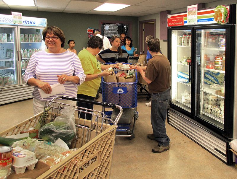 Photo Credit: OUTLOOK PHOTO: BEVERLY CORBELL - Judy Allen, executive director of SnowCap Community Charities, helps visitors select groceries.