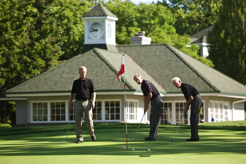 Photo Credit: TRIBUNE PHOTO; JAIME VALDEZ - Marvin French (left) watches fellow Pumpkin Ridge co-founders Gay Davis and Barney Hyde putt on the 18th green of the Witch Hollow course.