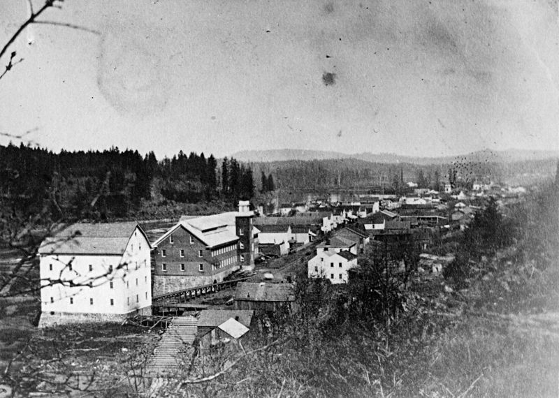 Photo Credit: PHOTO COURTESY: OREGON HISTORICAL SOCIETY - Late 1864 or early 1865 photo of the new Oregon City Woolen Mills, and the Imperial Mills, just before construction of the steamboat basin. Planked water flume in foreground leads from Willamette Falls to Imperial Mills. Elevated ramp in rear of Imperial Mills leading down to Woolen Mills is likely the Canemah horse railroad. McLoughlin House is opposite Woolen Mills tower.