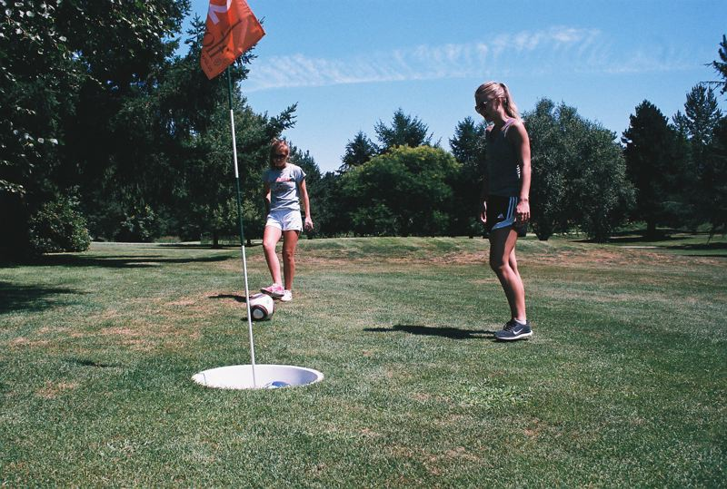 Photo Credit: PHOTO BY JOHN DENNY - Tayler McCamman putts on the second FootGolf hole at Sah-Hah-Lee, while Tahni Harr looks on. The FootGolf cup is 21 inches in diameter and players use a standard soccer ball.