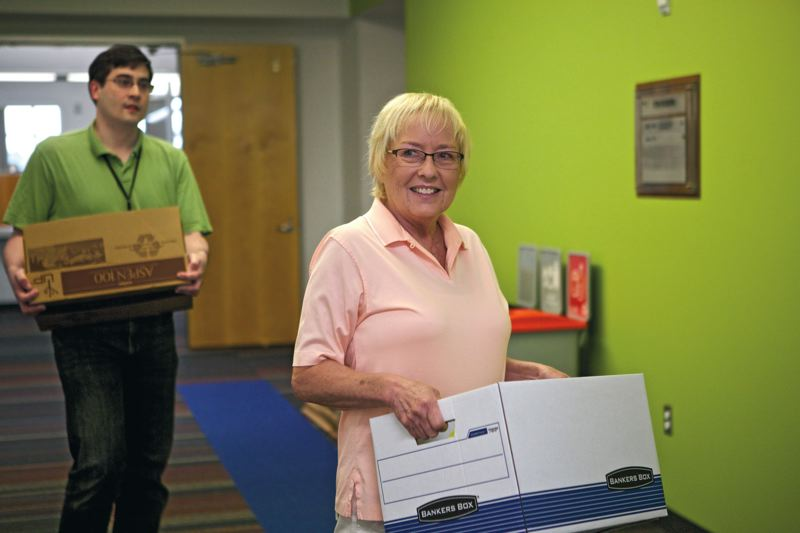 Photo Credit: TIMES PHOTO: JAIME VALDEZ - City of Beaverton human resource employees Gaye Fortier and Marty May carry boxes to their new desks at the Beaverton Building on Friday.