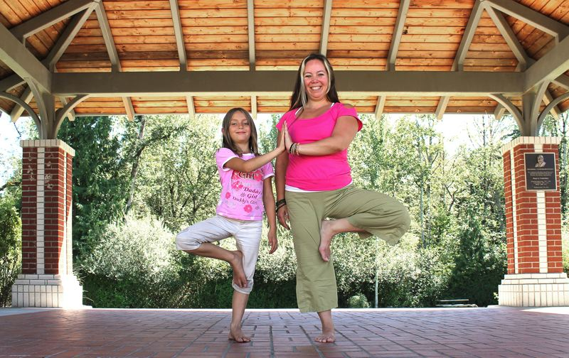 Photo Credit: OUTLOOK PHOTO: CARI HACHMANN - Kris Myers and her daughter, Cheyenne, practice the tree pose under the gazebo at Fairview Community Park.