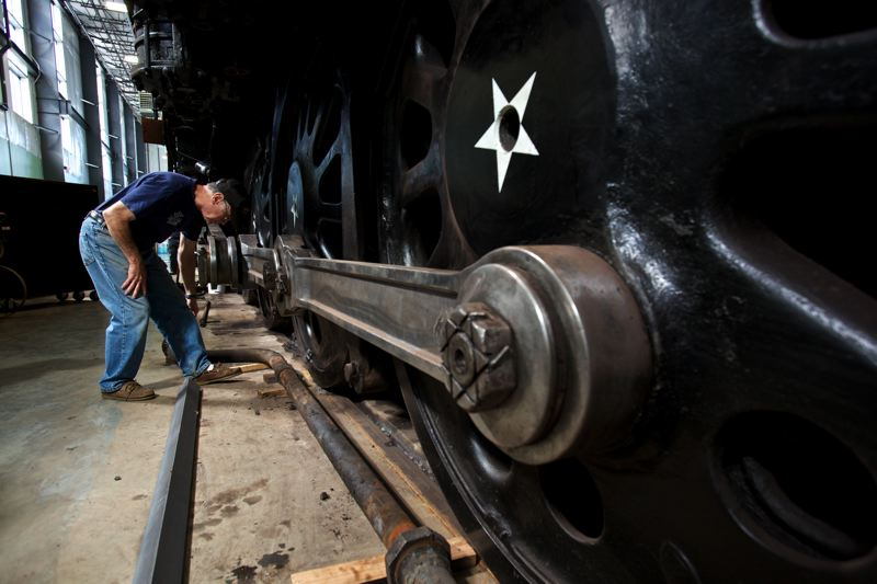 Photo Credit: TIMES PHOTO: JAIME VALDEZ - Mark Kramer, president of the nonprofit Friends of 4449 Inc., looks at the side rods and drive wheels of the locomotive