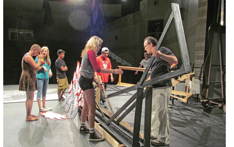 Photo Credit: PHOTO BY: DICK TRTEK - Co-director Kirk Mouser, far right, constructs the set for IMHO, with help from, from left, Madie, Tessa, Omar, Emily and Roy.