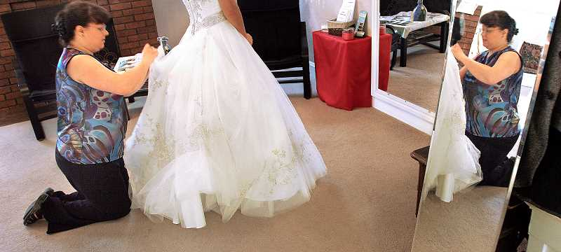 Photo Credit: OUTLOOK PHOTO: JIM CLARK - Davis bustles the back of a wedding dress, making the gown look fuller for the bride-to-be.