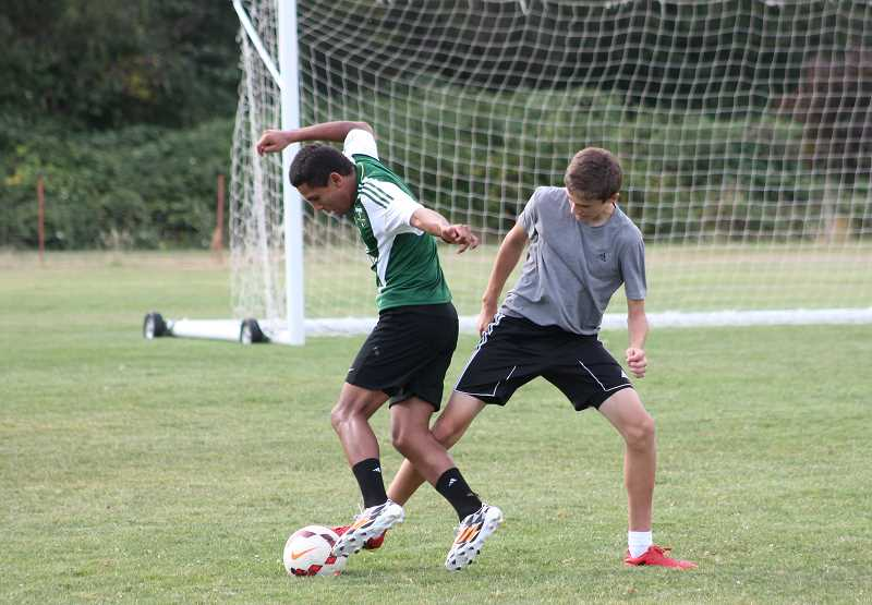 Photo Credit: JIM BESEDA/MOLALLA PIONEER - Fortino Media (left) tries to work the ball past Damon Seward as several players with the Molalla boys' soccer team went through a voluntary workout last week.
