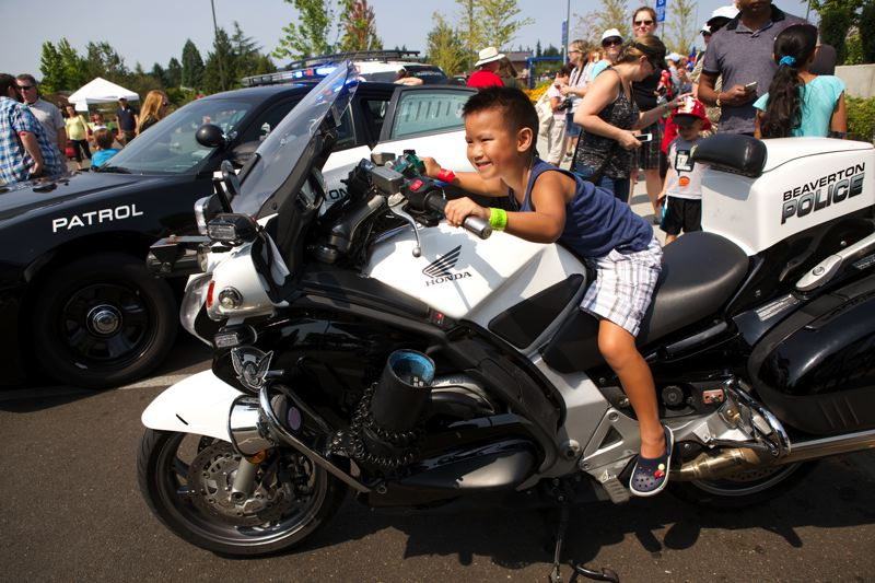 Photo Credit: TIMES PHOTO: JAIME VALDEZ - Brandon Ma, 5, of Beaverton tests out a Beaverton Police Department motorcycle.