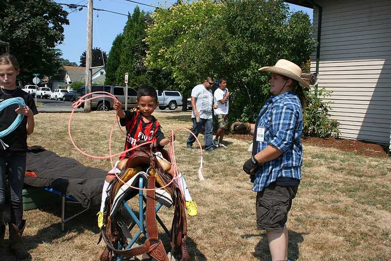 The 4-H Wagon Train set up an interactive display including this saddle where people could perch and practice roping a dummy cows head (not pictured), with advice from a staff member.