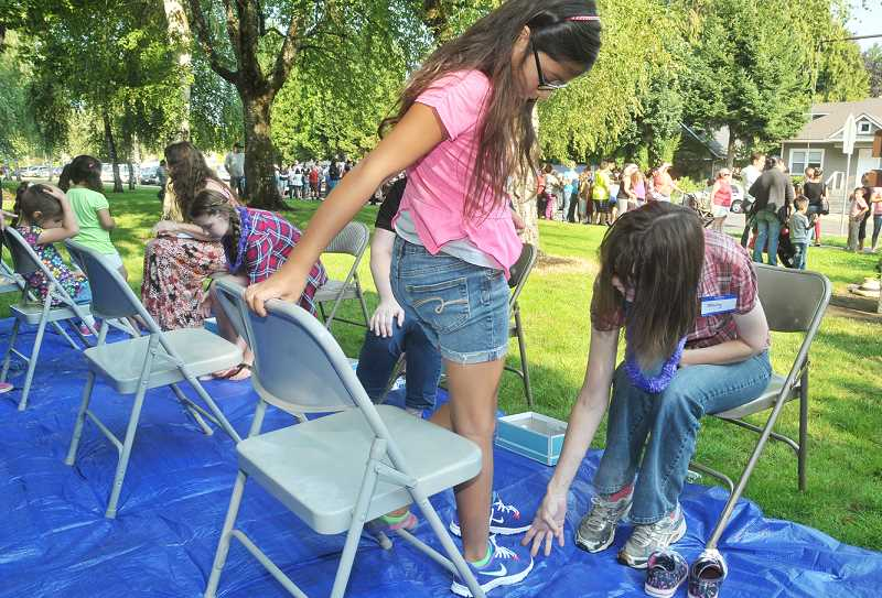 Photo Credit: GARY ALLEN - A Newberg youth tries on a pair of shoes at the annual giveaway Saturday at the Newberg School District headquarters. The event, in its second year, is sponsored by The Roots church and meted nearly 200 pairs.
