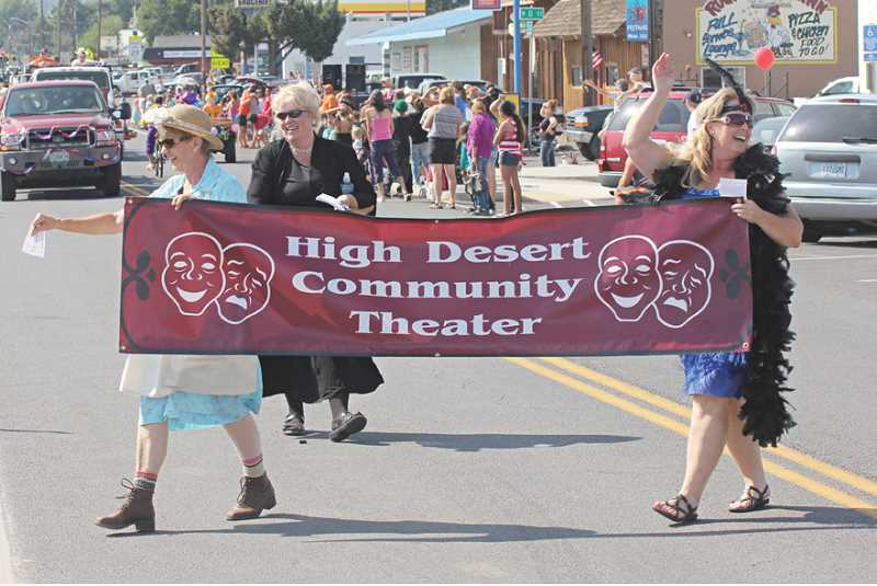 Photo Credit: JEFF WILSON - High Desert Community Theater members, left to right, Jan McDonald, Joy DeHaan, and Teri Drew carry the group's banner.
