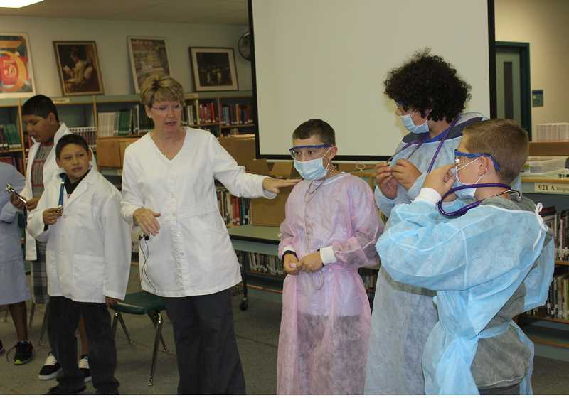Photo Credit: SUSAN MATHENY/MADRAS PIONEER - Michele Decker, with COCC's nursing program, explains the different outfits worn by nursing students in the many occupations open to them during a Junior Buffalo Academy session.
