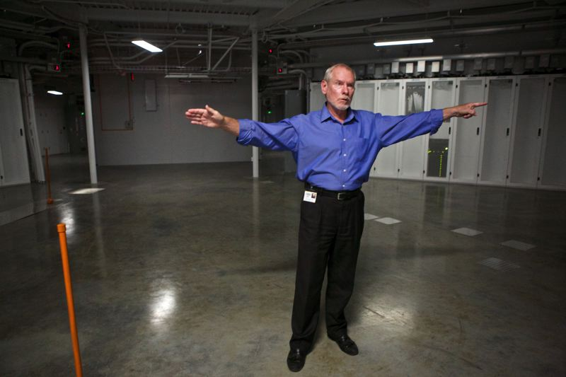 Photo Credit: TIMES PHOTO: JAIME VALDEZ - Perry Gliessman points in both directions to where racks of servers are cooled inside OHSU's new Data Center West in Aloha.