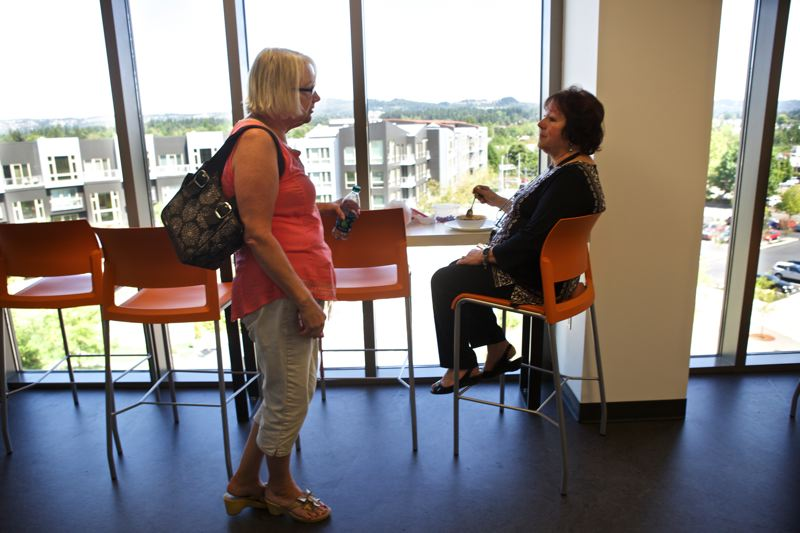 Photo Credit: TIMES PHOTO: JAIME VALDEZ - Cathy Jack, who works in the city of Beaverton's engineering department, and Debbie Baidenmann, records manager in the city attorney's office, chat during lunch in the fourth-floor cafe of the Beaverton Building, which serves as the city's new administrative center.