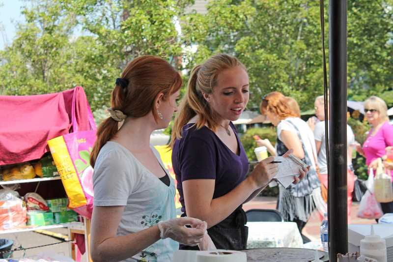 Photo Credit: REVIEW PHOTO: JILLIAN DALEY - Haley Russell (right) runs her creperie stand Saturday while friend and supporter Alexis Smead works by her side. Haleys mom, Nikii Davis (not pictured), also was on hand.