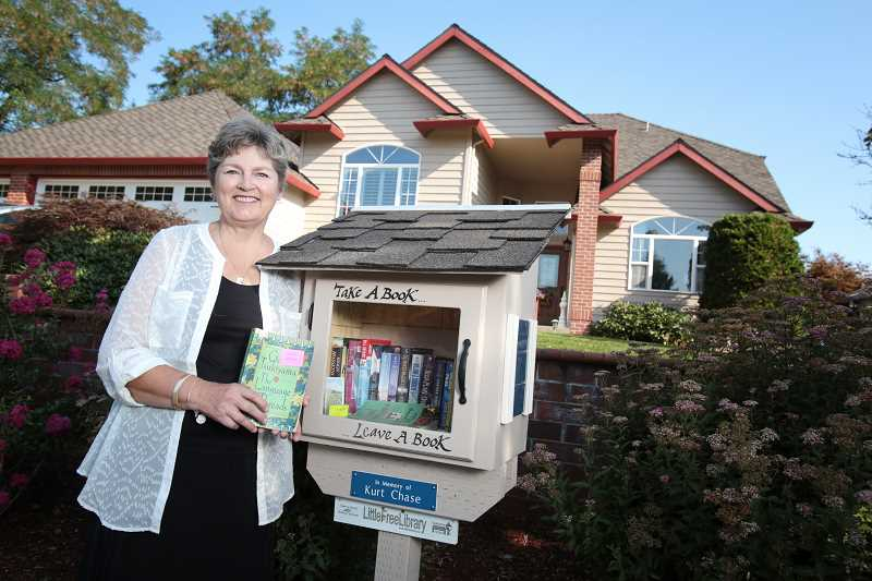 Photo Credit: TIMES PHOTO: JONATHAN HOUSE - Barb Zahler opened a small library outside her Bull Mountain home earlier this year. The library is part of the Little Free Library program, which has spread all over the world since it began in 2009
