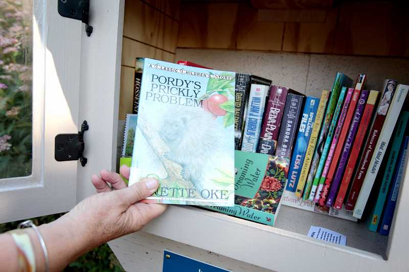 Photo Credit: TIMES PHOTO: JONATHAN HOUSE - Barb Zahler keeps a mix of adult and childrens books in her Little Free Library in Tigard.